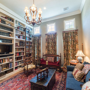 Living room library - small traditional open concept terra-cotta floor living room library idea in Houston with beige walls, no fireplace and a tv stand