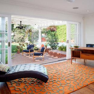 Imagen de salón abierto, clásico, grande, con paredes blancas y suelo de madera en tonos medios