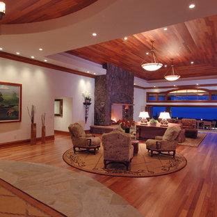 Großes, Repräsentatives, Fernseherloses, Offenes Modernes Wohnzimmer mit Kaminumrandung aus Stein, weißer Wandfarbe, braunem Holzboden, Kamin und braunem Boden in Hawaii