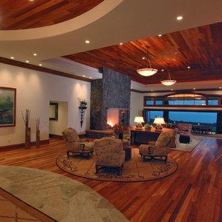 Imagen de salón para visitas abierto, actual, grande, sin televisor, con marco de chimenea de piedra, paredes blancas, suelo de madera en tonos medios, chimenea tradicional y suelo marrón