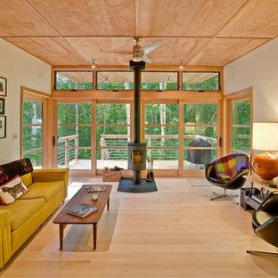 Immagine di un soggiorno minimal con parquet chiaro e stufa a legna