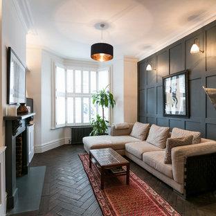 Immagine di un soggiorno chic con parquet scuro, camino classico e pareti grigie