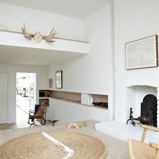 Foto di un soggiorno nordico aperto con pareti bianche, parquet chiaro, camino classico, cornice del camino in mattoni e nessuna TV