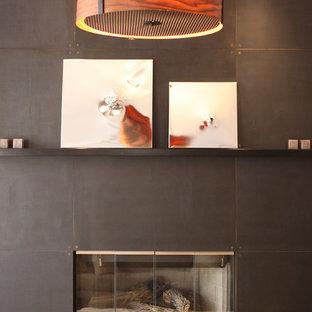 ニューヨークの中サイズのコンテンポラリースタイルのおしゃれなリビングロフト (フォーマル、マルチカラーの壁、カーペット敷き、標準型暖炉、コンクリートの暖炉まわり、テレビなし) の写真