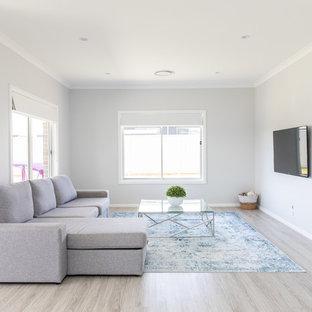 Modelo de salón abierto, minimalista, grande, con paredes grises, suelo vinílico, televisor colgado en la pared y suelo gris