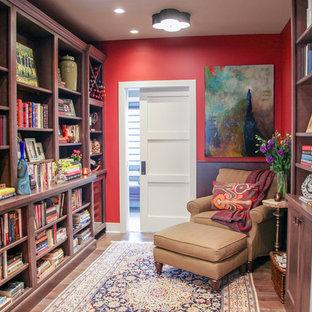 Esempio di un piccolo soggiorno eclettico chiuso con libreria, pareti rosse, pavimento in legno massello medio, nessun camino, cornice del camino in pietra e nessuna TV