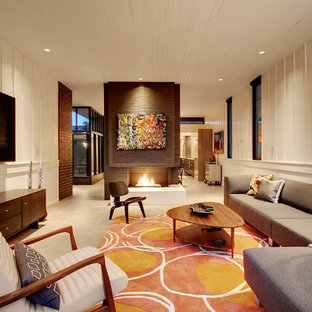 シアトルの中サイズのミッドセンチュリースタイルのおしゃれな独立型リビング (白い壁、標準型暖炉、レンガの暖炉まわり、壁掛け型テレビ、コンクリートの床、グレーの床) の写真