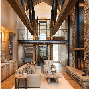 Aménagement d'un grand salon montagne ouvert avec une salle de réception, un mur beige, un sol en bois brun, une cheminée standard, un manteau de cheminée en métal, un sol marron et un téléviseur fixé au mur.