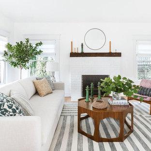 Ejemplo de salón para visitas cerrado, retro, de tamaño medio, con paredes blancas, suelo de madera clara, chimenea tradicional, marco de chimenea de ladrillo, televisor colgado en la pared y suelo beige