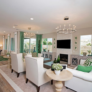 Inspiration for a transitional open concept medium tone wood floor living room remodel in Los Angeles with gray walls, a standard fireplace, a stone fireplace and a wall-mounted tv
