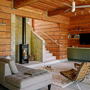 Living room - contemporary concrete floor living room idea in San Francisco with a wall-mounted tv and a wood stove
