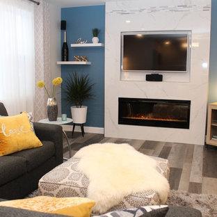 Diseño de salón abierto, moderno, de tamaño medio, con paredes azules, suelo laminado, chimenea tradicional, marco de chimenea de baldosas y/o azulejos, pared multimedia y suelo gris