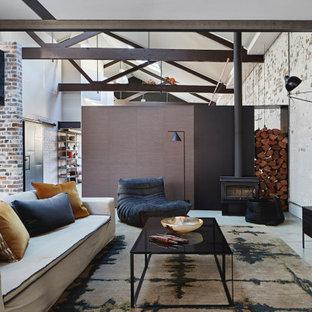 Idée de décoration pour un salon urbain avec béton au sol, un poêle à bois, un plafond voûté et un mur en parement de brique.