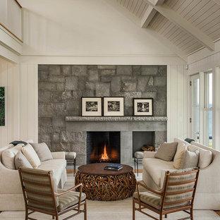 Foto de salón para visitas abierto, costero, grande, con paredes blancas, suelo de madera clara, chimenea tradicional y marco de chimenea de piedra
