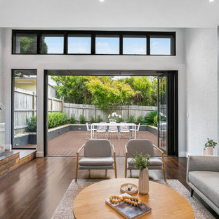 Photo of a large contemporary open concept living room in Sydney with white walls, medium hardwood floors and brown floor.