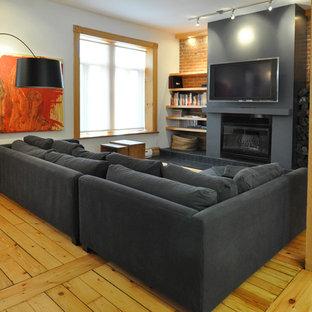 Idee per un soggiorno contemporaneo con pavimento in legno massello medio, TV a parete e pavimento giallo