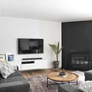Immagine di un soggiorno moderno di medie dimensioni e aperto con pareti bianche, pavimento in legno massello medio, camino ad angolo, cornice del camino in metallo, TV a parete e pavimento nero