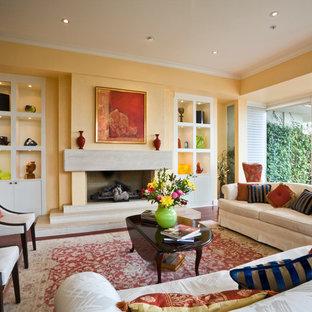 バンクーバーの広いトランジショナルスタイルのおしゃれなLDK (黄色い壁、標準型暖炉、フォーマル、無垢フローリング、コンクリートの暖炉まわり) の写真
