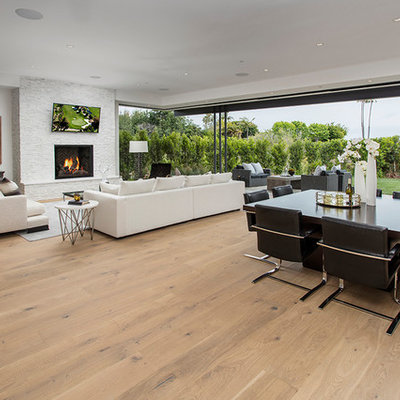 Living room - large 1960s open concept medium tone wood floor and brown floor living room idea in Orange County with white walls, a standard fireplace, a brick fireplace and a wall-mounted tv