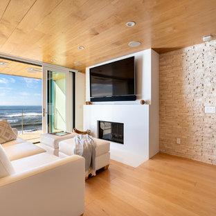 ロサンゼルスの巨大なコンテンポラリースタイルのおしゃれなLDK (白い壁、淡色無垢フローリング、標準型暖炉、石材の暖炉まわり、壁掛け型テレビ、黄色い床) の写真