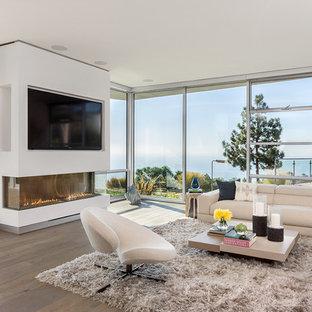 ロサンゼルスの広いコンテンポラリースタイルのおしゃれなLDK (白い壁、淡色無垢フローリング、標準型暖炉、漆喰の暖炉まわり) の写真