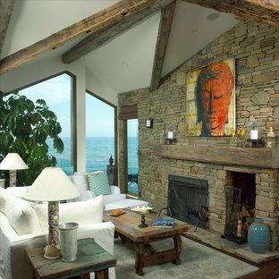 ロサンゼルスのビーチスタイルのおしゃれなLDK (マルチカラーの壁、濃色無垢フローリング、標準型暖炉、石材の暖炉まわり、茶色い床) の写真