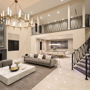 Example of a large trendy formal and open concept porcelain floor and gray floor living room design in Los Angeles with beige walls, a standard fireplace, a stone fireplace and no tv