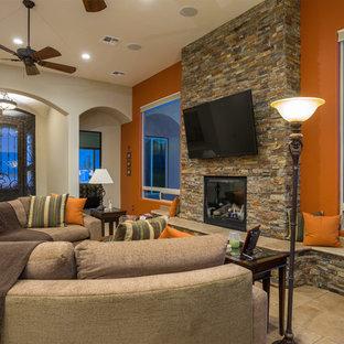 Ejemplo de salón abierto, moderno, grande, con parades naranjas, suelo de baldosas de cerámica, todas las chimeneas, marco de chimenea de piedra y televisor colgado en la pared