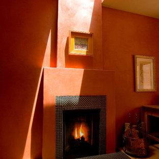 ロサンゼルスの中くらいの地中海スタイルのおしゃれなLDK (オレンジの壁、淡色無垢フローリング、標準型暖炉、タイルの暖炉まわり、黒い床) の写真