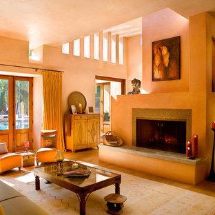 Esempio di un soggiorno mediterraneo di medie dimensioni e aperto con pareti arancioni, parquet chiaro, camino classico, cornice del camino piastrellata e pavimento nero
