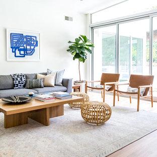 Immagine di un soggiorno moderno aperto con pareti bianche, pavimento in legno massello medio, camino bifacciale, cornice del camino piastrellata e pavimento marrone