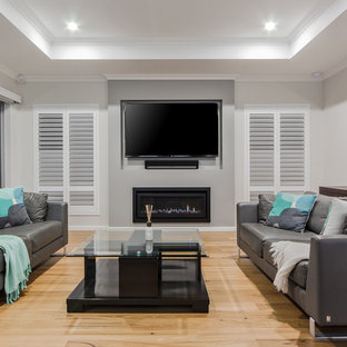 This is an example of a contemporary formal enclosed living room in Perth with grey walls, light hardwood floors, a ribbon fireplace, a wall-mounted tv and beige floor.