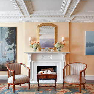ニューヨークの広いトラディショナルスタイルのおしゃれな独立型リビング (フォーマル、オレンジの壁、濃色無垢フローリング、標準型暖炉、木材の暖炉まわり、テレビなし) の写真