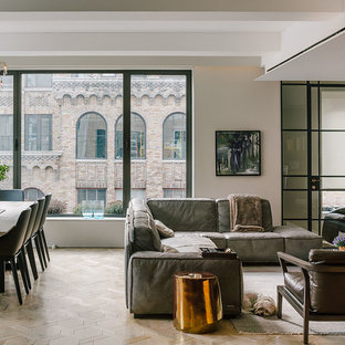 Example of a large trendy open concept and formal light wood floor and beige floor living room design in New York with gray walls, no fireplace and a wall-mounted tv