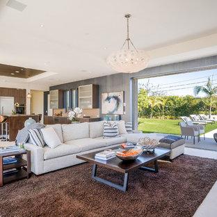 ロサンゼルスの大きいコンテンポラリースタイルのおしゃれなLDK (フォーマル、オレンジの壁、ライムストーンの床、横長型暖炉、石材の暖炉まわり、壁掛け型テレビ、白い床) の写真