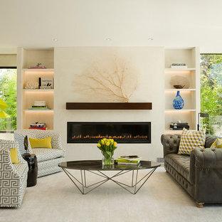 ロサンゼルスの大きいビーチスタイルのおしゃれなLDK (フォーマル、白い壁、淡色無垢フローリング、横長型暖炉、漆喰の暖炉まわり、テレビなし) の写真