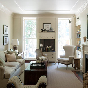 Example of a mid-sized classic enclosed dark wood floor living room design in New York with beige walls, a standard fireplace and no tv