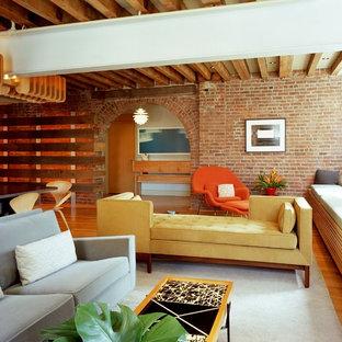 Foto di un grande soggiorno industriale con pavimento in legno massello medio