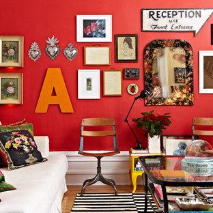 ニューヨークのエクレクティックスタイルのおしゃれなリビング (赤い壁、無垢フローリング) の写真