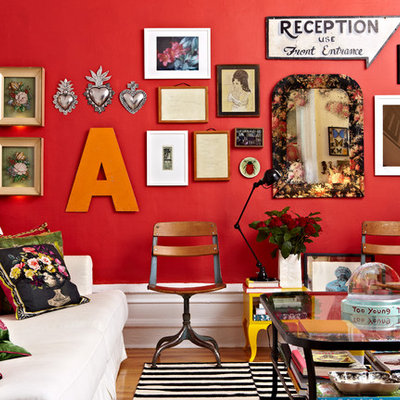 Eclectic medium tone wood floor living room photo in New York with red walls