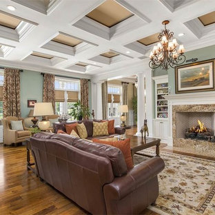 Design ideas for an expansive traditional enclosed living room in Orlando with a library, green walls, medium hardwood floors, a standard fireplace, a stone fireplace surround, no tv and brown floor.