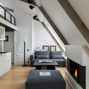 Imagen de salón para visitas nórdico, pequeño, con paredes blancas, suelo de madera clara, marco de chimenea de yeso y chimenea lineal