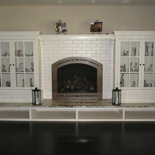 中サイズのトラディショナルスタイルのおしゃれな独立型リビング (フォーマル、ベージュの壁、濃色無垢フローリング、標準型暖炉、レンガの暖炉まわり、テレビなし、白い床) の写真