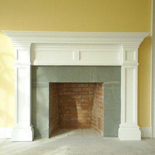 Mid-sized traditional formal open concept living room in New York with yellow walls, a standard fireplace, a metal fireplace surround, concrete floors, no tv and grey floor.