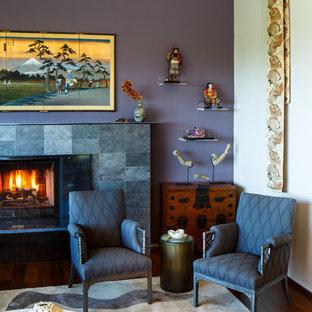 Exemple d'un salon asiatique de taille moyenne et ouvert avec un mur violet, une cheminée standard, un manteau de cheminée en pierre, une salle de réception, aucun téléviseur et un sol en bois foncé.