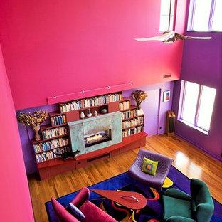 Modelo de salón abierto, bohemio, grande, con paredes rosas, suelo de madera en tonos medios y chimenea lineal