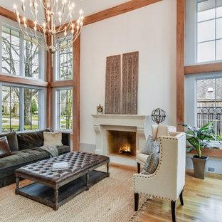 Klassisk inredning av ett separat vardagsrum, med vita väggar, mellanmörkt trägolv, en standard öppen spis, en spiselkrans i gips och brunt golv