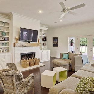 ニューオリンズの広いビーチスタイルのおしゃれなLDK (白い壁、濃色無垢フローリング、標準型暖炉、レンガの暖炉まわり、壁掛け型テレビ) の写真
