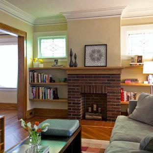 Foto de salón clásico renovado, de tamaño medio, con paredes amarillas, suelo de madera en tonos medios, chimenea tradicional y marco de chimenea de ladrillo
