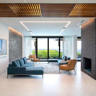 マイアミのコンテンポラリースタイルのおしゃれなLDK (白い壁、標準型暖炉、石材の暖炉まわり、白い床) の写真